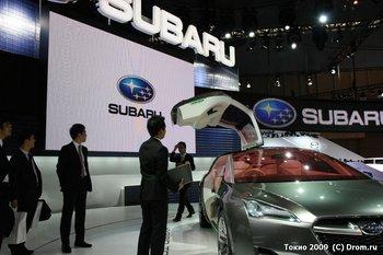 Subaru Tourer Hybrid. Прямо под нижнм углом двери стои сотрудник компании Subaru