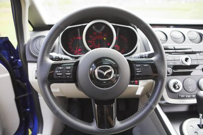 Руль у CX-7 небольшой, удобный в использовании. Но качество его покрытия (а тут, судя по каталогу, натуральная кожа) оставляет легкое недоумение — не кожзам ли это.