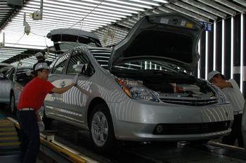 Сборочная линия на японском заводе Цуцуми (компания Toyota). На переднем плане — леворульный Toyota Prius для рынка США. Для японского рынка Toyota Prius комплектуется передней оптикой без желтых линз указателей поворота. На заднем плане — Toyota Camry.