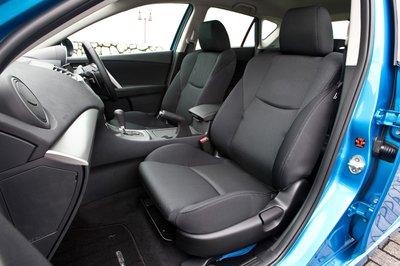 Руль регулируется по углу наклона (43 мм вверх-вниз) и телескопически (50 мм вперёд-назад). Сиденья стали больше и регулируются в пределах 55 мм по вертикали и 260 мм по горизонтали. На фото — спортивные сиденья, которыми в стандарте комплектуются хэтчбэк 20S, седан 20E и Mazdaspeed Axela.