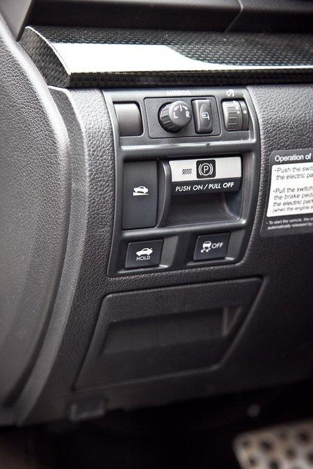 Ручник включается тут. А также отключается система стабилизации, задействуется опционная система помощи при старте в горку, открывается багажник, складываются и настраиваются зеркала.