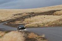 Коричневые холмы, черная машина, сияющие фары.