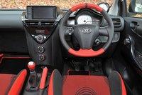 Место водителя выглядит по-спортивному. Верхняя и нижняя части рулевого колеса, а также ручка переключателя передач выполнены из натуральной кожи красного цвета. На приборной панели можно увидеть спидометр с разметкой до 200 км/ч и эксклюзивный тахометр.