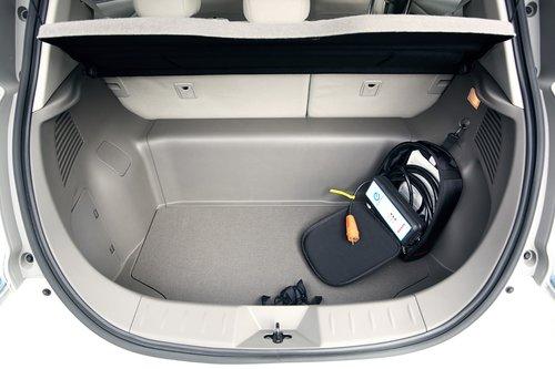 Объем багажника 330 л. Основное неудобство для багажа — широкая перемычка между задними колесными арками (под ней расположен конденсаторный блок). Тем не менее, спинка заднего сиденья складывается целиком или по частям. В сумке — зарядное устройство для подключения Leaf к бытовой электророзетке