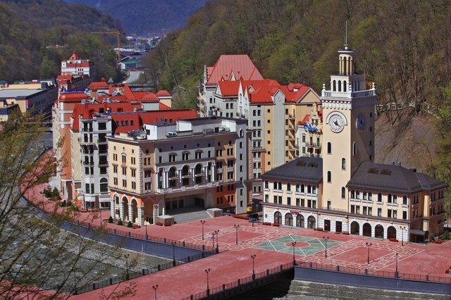 Гостиничный комплекс «Роза хутор» проектировали голландские архитекторы, оттого он смотрится несколько по-европейски, хотя на переднем плане, в здании с башней, угадываются очертания Центрального сочинского вокзала