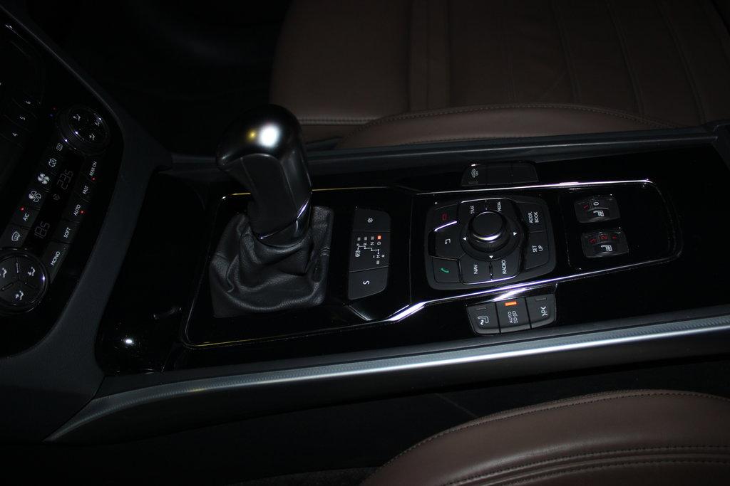 """Всё под рукой. Слева и справа от круглой кнопки-шайбы: Кнопка включения массажа поясничной области; Кнопка включения автоматического переключения с ближнего света на дальний и наоборот; Кнопка включения устройства оценки размеров парковочного места (влезем или нет); Кнопка отключения заводской сигнализации. И две заглушки, на месте которых в Европе стоят кнопка вызова помощи на дорогах и кнопка вызова экстренных служб. Ниже кнопки-шайбы расположены трёхступечатые крутилки обогрева передних сидений. Кнопка-шайба с россыпью окруживших её подружек отвечают за всё, кроме обогрева салона. Рычаг АКПП (Aisin AM-6) меется наглядное отображение выбранного режима работы. Ниже рычага две кнопки: \""""Спортивный лев\"""" и \""""Мягкие, цепкие лапы\"""". Снежный режим позволяет начинать движение с третьей передачи и здорово помогает, когда это надо, за счёт свой плавности и старанием во что бы то ни стало не допустить проворачивания ведущих колёс на поверхности. Спортивный крутит двигатель до отсечки и переключается при смене передач быстрее. К общим достоинствам можно отнести умение тормозить двигателем."""