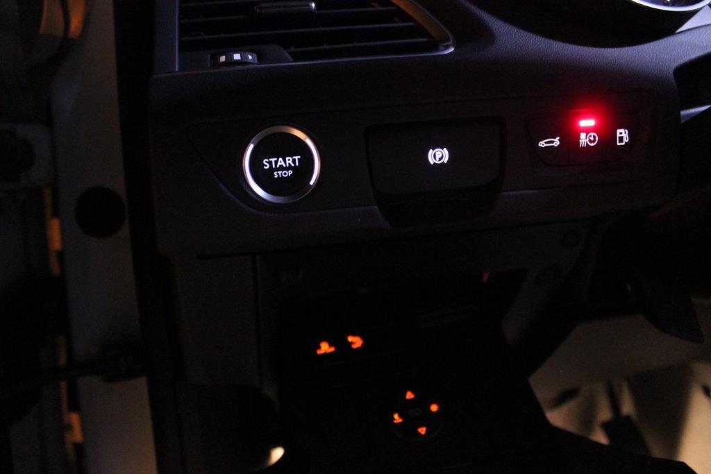 Удобная кнопка, позволяющая запускать мотор, не садясь в автомобиль. Правее неё кнопка автоматического электромеханического стояночного тормоза. Ниже виднеются раположенные в откидном ящике кнопки отключения ESP и парктроников. С ними соседствуют кнопки управления цветным проекционным Head-up дисплеем, который расположен возле лобового стекла в поле зрения водителя.
