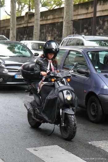 Симпатичная на мотороллере с сотовым телефоном. Светофоры в Париже довольно медленные, можно легко успеть отправить SMS.
