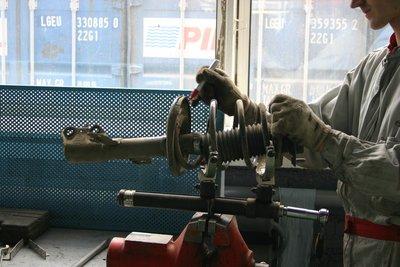 Снимаем пружину. Механик метит маркером положение пружины относительно опорной чашки стойки