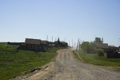 Вот таким образом федеральная трасса проходит через деревни. Люди существуют в постоянной дикой пыли. Движение не прекращается никогда.