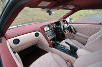 Пример отделки интерьера в розовых тонах, вызвавшей бурную реакцию на презентации GT-R2011. Приборная панель, центральная консоль и потолок обиты алькантарой. Эмблема на руле представляет собой традиционное японское лакированное украшение, даже бардачок обит натуральной кожей. Салон может быть окрашен в белые «Ultimate opal white» (525000иен, около $6400), серебристые «Ultimate metallic silver» (315000иен, около $3800) и другие тона.