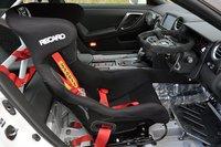 Для лучшего сцепления с поверхностью дороги модель оснащена гоночными сликами. Имеется буксировочный крюк, защелка капота, новый передний спойлер, регулируемая подвеска. Крышка багажного отдела выполнена из углеродного волокна. Система охлаждения машины дополнена кулерами дифференциала и воздухоотводом для охлаждения тормозов. Опционально автомобиль может быть укомплектован более производительными тормозами, а также системами ECM, TCM и ABS/VDC. Корпус защищен 6-точечным каркасом безопасности. Центральная консоль и обивка дверей выполнены из углеродного волокна. Для обеспечения пожарной безопасности автомобиль оснащен огнетушителем. Имеется также маршрутный компьютер от NISMO.