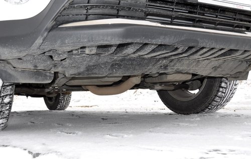 «Голая правда» кроссовера с 2,5-литровым двигателем: снизу моторный отсек почти не прикрыт, к тому же из-за переднего расположения выпускного тракта его труба заметно торчит снизу, заодно как бы являясь «силовой защитой» поддонов