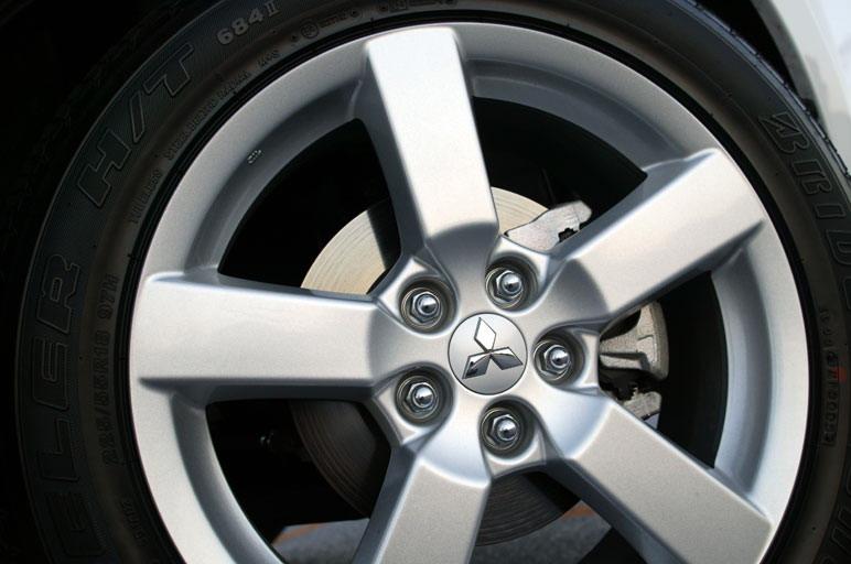Модификация G стандартно укомплектована алюминиевыми дисками размером 18 дюймов, изображенными на снимке. Кстати сказать, автомобиль Outlander M «обут» в шины размером 16 дюймов, а диски на нем  стальные. Размер шин  - 225/55R/18. Даже если ставить всесезонные покрышки типа Mud&Snow, то, несмотря на свой большой диаметр, за счет своего низкого профиля они обеспечивают машине мягкий, плавный ход.